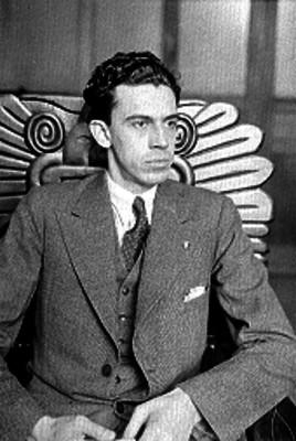 Hombre elegante sentado en una silla labrada con motivos prehispánicos, retrato