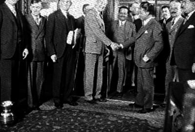 Funcionario público estrecha la mano de un empleado ante varios empleados públicos en una oficina pública, retrato