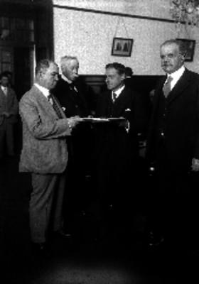 Miembros de la Cámara de Comercio recibiendo documentos