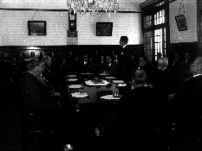 Hombres haciendo uso de la palabra durante una reunión en la Cámara de Comercio