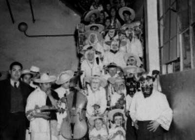 Individuos vestidos con traje regional tarasco y músicos en un patio, retrato