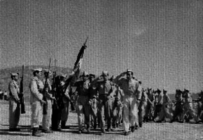 Grupo de conscriptos desfilando frente a una escolta en un campo militar