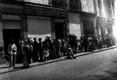 """Fila de gente en la calle entrando a un edificio del departamento de Salubridad Pública, Oficina de Vacunación """"Dr. Balmis"""""""