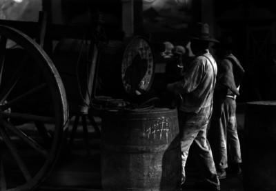 Hombres estiban barriles de pulque a una carreta
