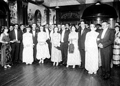 Francisco R. Serrano, acompañado de mujeres que portan abanicos de plumas durante un evento social