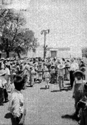 Niño trepando a un palo encebado ante la mirada de la gente en un parque