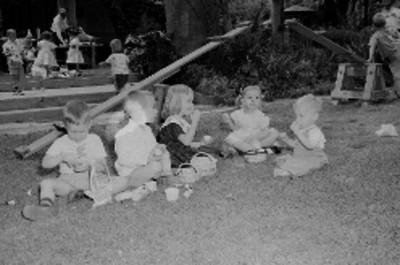 Niños sentados en el pasto, comiendo dulces