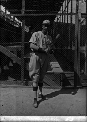 Aguilar, beisbolista cubano, sostiene un bat en un estadio, retrato