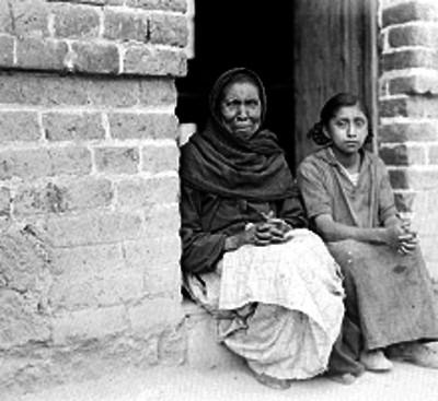 Anciana con niña, sentadas en el escalón de una puerta de una vivienda, de condición humilde