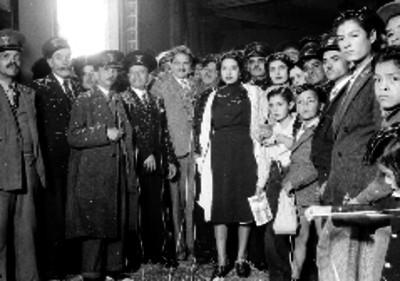 Empleados del servicio postal y familiares durante una celebración del día del cartero en un salón, retrato
