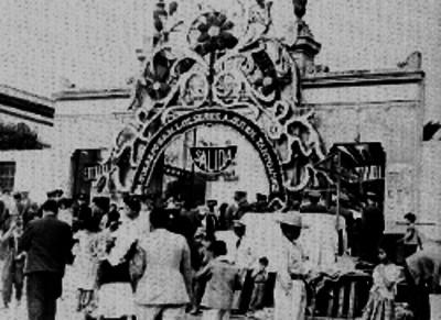 Grupo de personas a la entrada de un panteón adornando con flores probablemente durante un día de muertos
