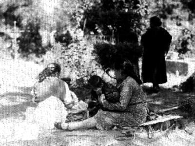 Mujeres y niños de condición media sentados en el piso junto a una tumba dentro de un panteón durante un día de muertos