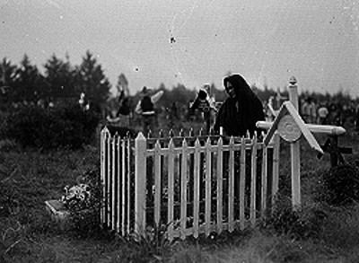Mujer cubierta con un rebozo parada junto a una tumba dentro de un panteón