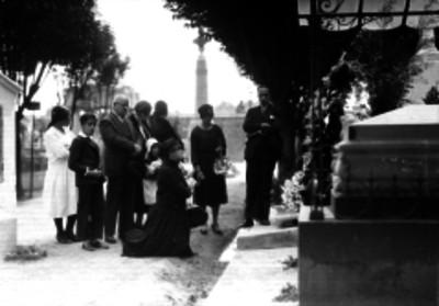 Personas reunidas frente a una tumba