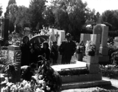 Personas reunidas junto a una tumba en un cementerio