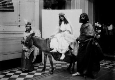 Individuos esceneficando a María y José, con un asno y una niña dentro de un edificio, retrato