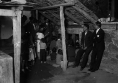 Familia en el patio de una casa durante una representación de los peregrinos en época navideña