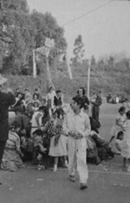 Niños y personas mayores en el rompimiento de una piñata durante una posada
