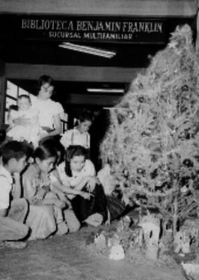Niños decorando el nacimiento y el árbol de navidad en la biblioteca Benjamín Franklin