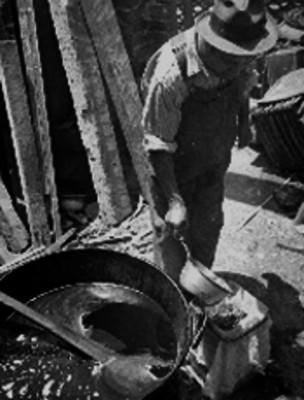 Hombre vestido con un overol calentando aceite en un perol para elaborar chicharrón