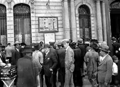 Individuos checando una lista de premios de la Lotería Nacional en un edificio público