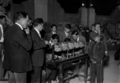Hombres celebrando un sorteo de Lotería Nacional en un parque con arquitectura estílo Art - deco
