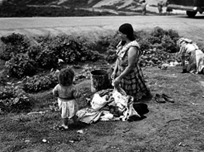 Mujeres pobres al lavar su ropa en lavaderos junto de un arroyo