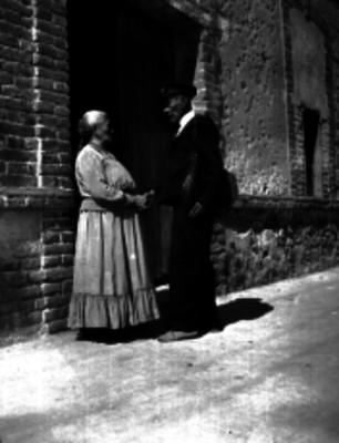 Cartero con su esposa posiblemente a la entrada de su hogar