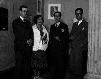 O'Gorman acompañado de individuos en una exposición de pinturas
