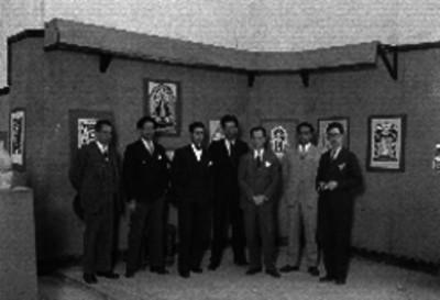 Pintores durante una exposición de pintura popular donde se muestran chinanpas, flores y una virgen