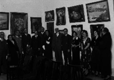 Individuos durante una exposición de bodegones y paisajes