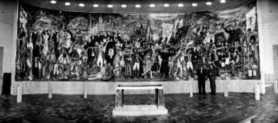 Hombres vestidos de traje junto al mural realizado por Juan O'gorman, retrato