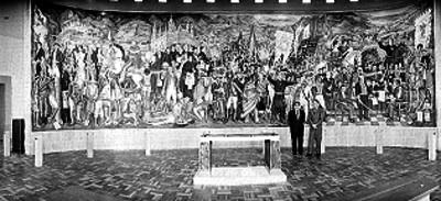 Individuos vestidos de traje posando junto al mural realizado por Juan O'gorman, retrato