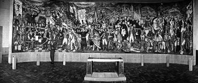 Individuos vestido de traje posando junto al mural realizado por Juan O'gorman