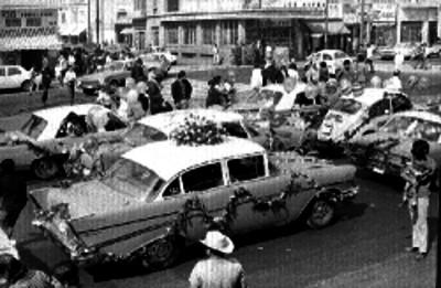 Personas y autos adornados de flores durante una peregrinación en la Cd. de México