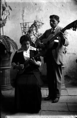 """""""Joaquín y María de Jesús Alfaro"""" con instrumentos de cuerda en un patio, retrato"""