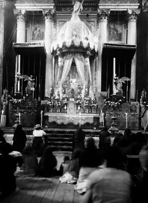 Feligrses hincados ante altar de una iglesia del siglo XIX