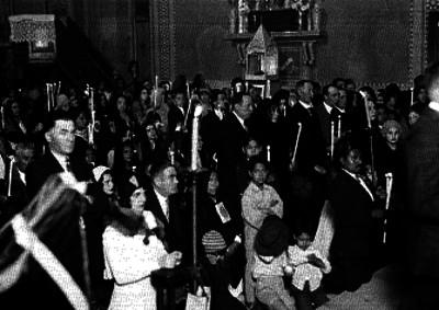 Personas con velas en las manos durante ceremonia en una iglesia