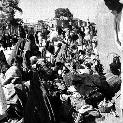 Mujeres y hombres campesinos sentados en la explanada de la basílica de Guadalupe