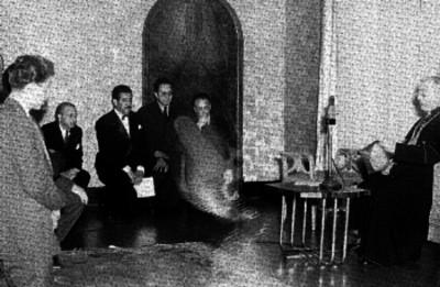 Villanueva, cardenal, lee documento ante varios hombres en interior de una iglesia