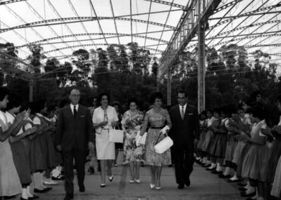 Carlos Amador y funcionarios son recibidos por niñas durante su visita a una escuela
