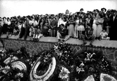 Personas aglomeradas sobre la barda del panteón durante el sepelio de Joaquín Amaro