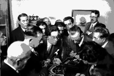 Alfonso Caso con otros individuos analizando figurillas arqueológicas de Monte Albán