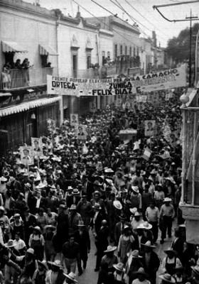 Juan Andrew Almazán candidato presidencial sobre un camión de carga en medio de una aglomeración de gente en una calle, durante su campaña en Querétaro