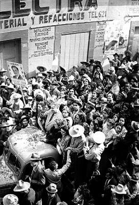 Juan Andrew Almazán transitando por una calle en un camión de carga en medio de una aglomeración de gente, durante su campaña en Querétaro