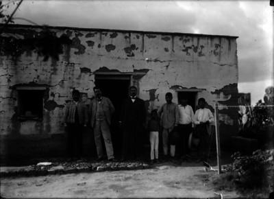 Hombres frente a una casa rustica