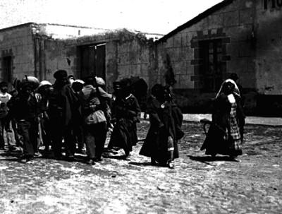 Revolucionarios acompañados de soldaderas caminan por una calle