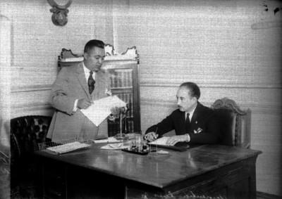Luis Armenta conversa con otro hombre en una oficina