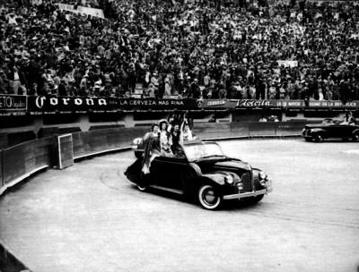 Mujeres con trajes andaluz dan la vuelta al ruedo en un automovil