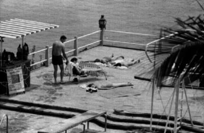 Turistas en una terraza playera, junto a una alberca